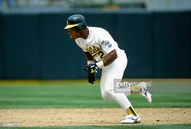 Outfielder Rickey Henderson of the Oakland Athletics takes off to steal third base against the New York Yankees during a Major League Baseball game...