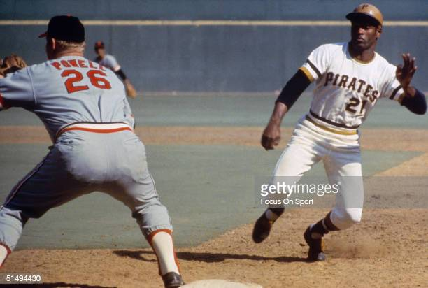 Outfielder Roberto Clemente of the Pittsburgh Pirates scampers back to first base as Boog Powell of the Baltimore Orioles reaches for the throw...