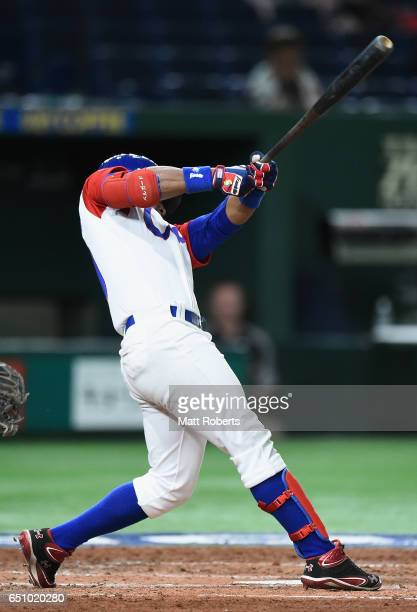 Outfielder Roel Santos of Cuba hits a single in the bottom of the third inning during the World Baseball Classic Pool B Game Five between Australia...