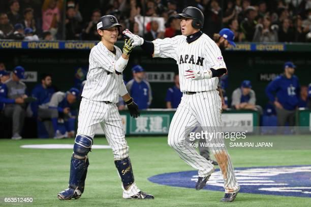 Outfielder Seiichi Uchikawa of Japan celebrates with Catcher Seiji Kobayashi after scoring a run by a RBI single of Infielder Nobuhiro Matsuda to...