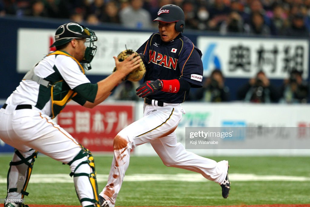 Outfielder Seiichi Uchikawa #24 of Japan tags out at home plate in the bottom half of the third inning during the international friendly game between Australia and Japan at Kyocera Dome Osaka on February 24, 2013 in Osaka, Japan.