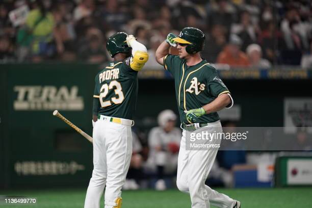 Outfielder Stephen Piscotty of the Oakland Athletics celebrates after hitting a solo homer with Infielder Jurickson Profar to make it 10 in the top...
