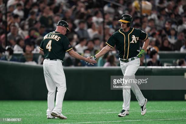 Outfielder Stephen Piscotty of the Oakland Athletics is congratulated after hitting a solo homer with third base coach Matt Williams to make it 10 in...