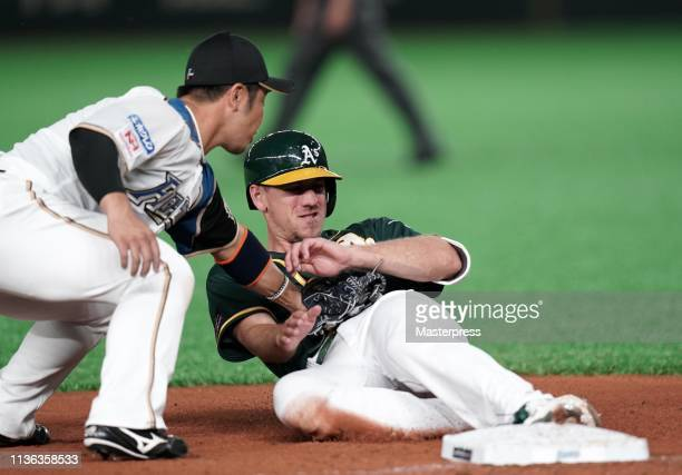 Outfielder Stephen Piscotty of the Oakland Athletics is tagged out on the third base in the top of 3rd inning during the game between Hokkaido...