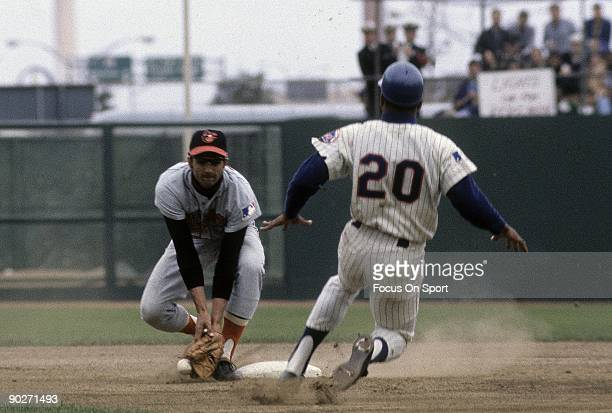 Outfielder Tommie Agee of the New York Mets slides into second as Mark Belanger of the Baltimore Orioles tries to make a play on the ball during a...