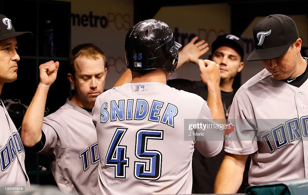 Outfielder Travis Snider #45 of the Toronto Blue Jays is congratulated after scoring against the Tampa Bay Rays during the game at Tropicana Field on August 2, 2011 in St. Petersburg, Florida.