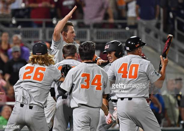 Outfielder Trevor Larnach of the Oregon State Beavers celebrates with his teammates after hitting a two run home run to give the Beavers a 53 lead in...