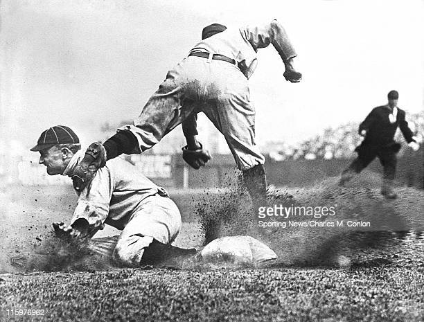 Outfielder Ty Cobb of the Detroit Tigers slides safely into third base as third baseman Jimmy Austin of the New York Yankees misses the throw from...