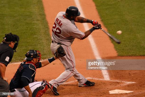 Outfielder Wily Mo Pena of the Boston Red Sox bats as catcher Victor Martinez of the Cleveland Indians and umpire Joe West look on during a game on...