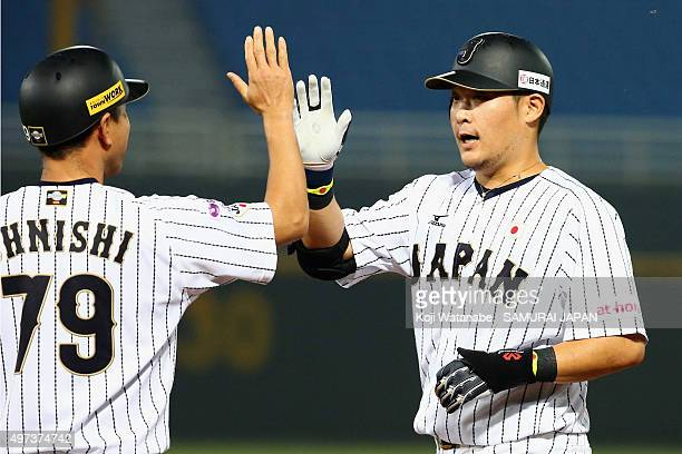 Outfielder Yoshitomo Tsutsugo of Japan high fives with the first base coach Takayuki Onishi after hitting a RBI single in the bottom of first inning...