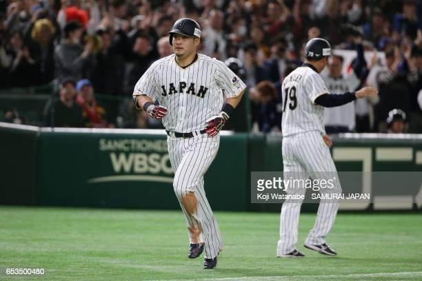 Outfielder Yoshitomo Tsutsugoh of Japan celebrates hitting a solo homerun with coach Takayuki Onishi to make it 01 in the bottom of the sixth inning...