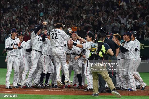 Outfielder Yuki Yanagita of Japan is congratulated by his team mates after hitting the game-ending two-run home run in the bottom of 9th inning...