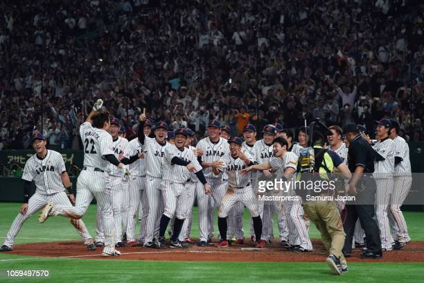 Outfielder Yuki Yanagita of Japan is congratulated by his team mates after hitting the gameending tworun home run in the bottom of 9th inning during...