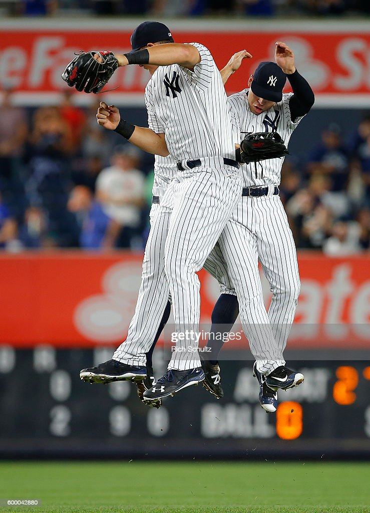 Outfielders Aaron Judge #99, Brett Gardner #11 and Jacoby Ellsbury #22 of the New York Yankees jump to celebrate their 2-0 win over the Toronto Blue Jays in a game at Yankee Stadium on September 7, 2016 in the Bronx borough of New York City.