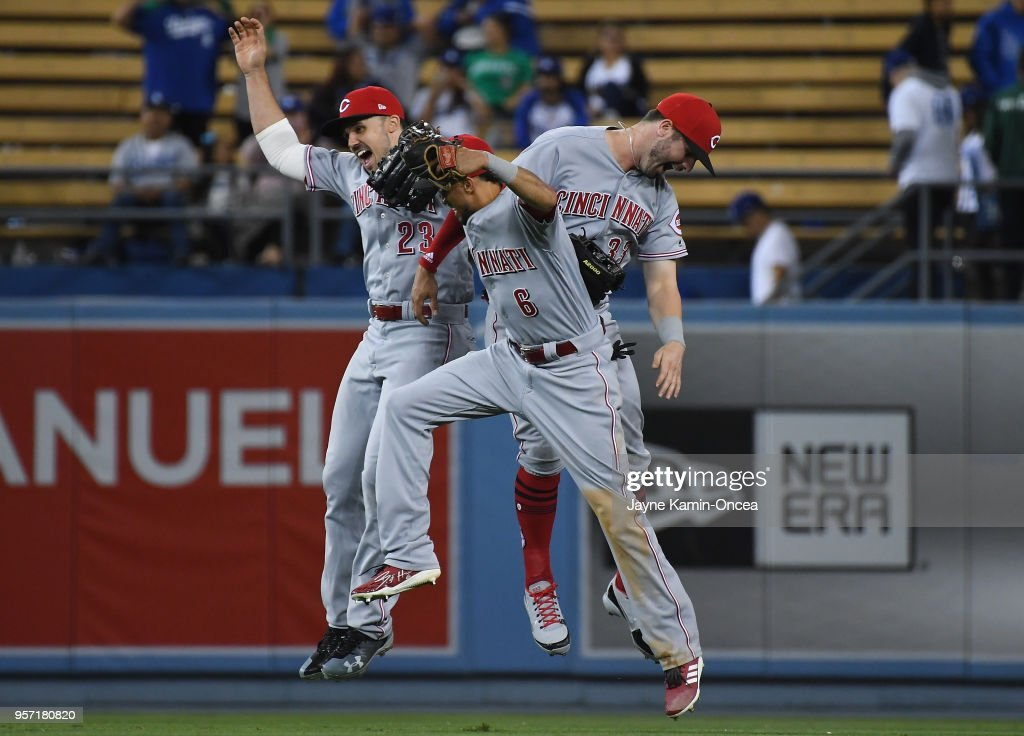 Outfielders Adam Duvall #23 Billy Hamilton #6 and Jesse Winker #33 of the Cincinnati Reds jump in the air as they celebrate defeating the Los Angeles Dodgers at Dodger Stadium on May 10, 2018 in Los Angeles, California.