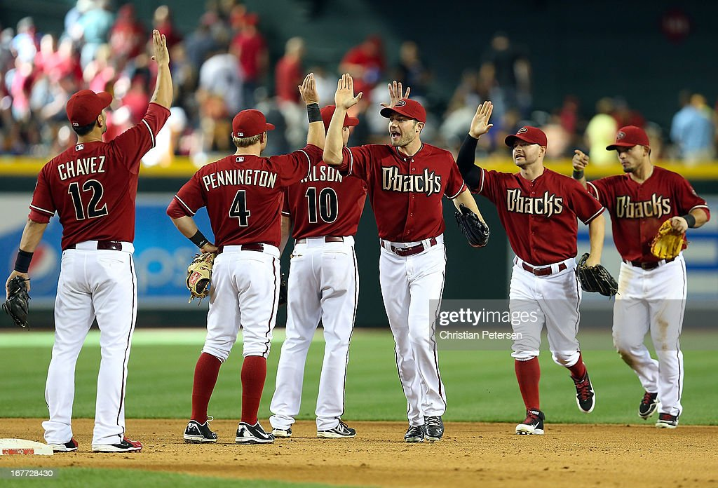 Outfielders A.J. Pollock #11, Cody Ross #7 and Gerardo Parra #8 of the Arizona Diamondbacks high-fives teamamtes after defeating the Colorado Rockies 4-2 in the MLB game at Chase Field on April 28, 2013 in Phoenix, Arizona.