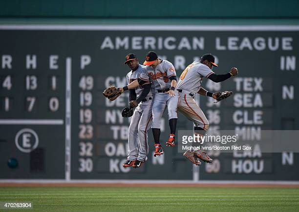 Outfielders Alejandro De Aza, David Lough and Adam Jones of the Baltimore Orioles celebrate a 4-1 victory over the Boston Red Sox at Fenway Park in...