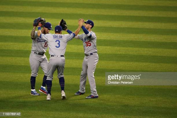 Outfielders Alex Verdugo Chris Taylor and Cody Bellinger of the Los Angeles Dodgers celebrate after defeating the Arizona Diamondbacks in the MLB...
