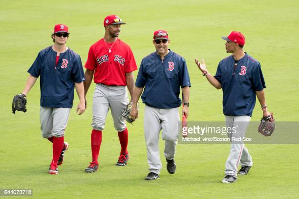 Outfielders Andrew Benintendi Chris Young and Mookie Betts of the Boston Red Sox walk off of the field with first base coach Ruben Amaro Jr during...