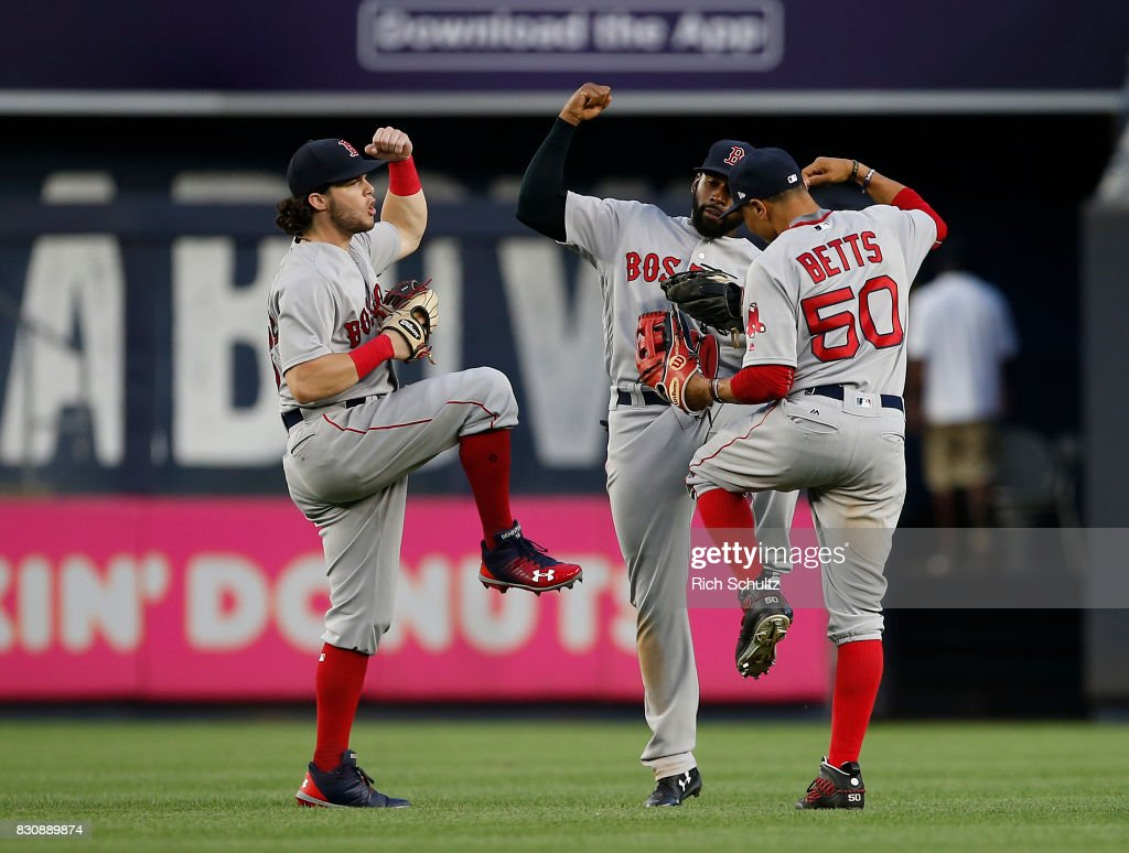 Outfielders Andrew Benintendi #16, Jackie Bradley Jr. #19 and Mookie Betts #50 of the Boston Red Sox celebrate after they defeat the New York Yankees 10-5 during a game at Yankee Stadium on August 12, 2017 in the Bronx borough of New York City.