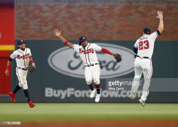 Outfielders Billy Hamilton, Ronald Acuna, Jr. #13 and Adam Duvall of the Atlanta Braves celebrate after the game against the San Francisco Giants at...