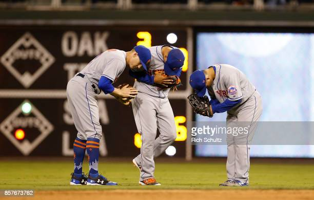 Outfielders Brandon Nimmo Juan Lagares and Norichika Aoki of the New York Mets bow to each other after defeating the Philadelphia Phillies 74 in 11...