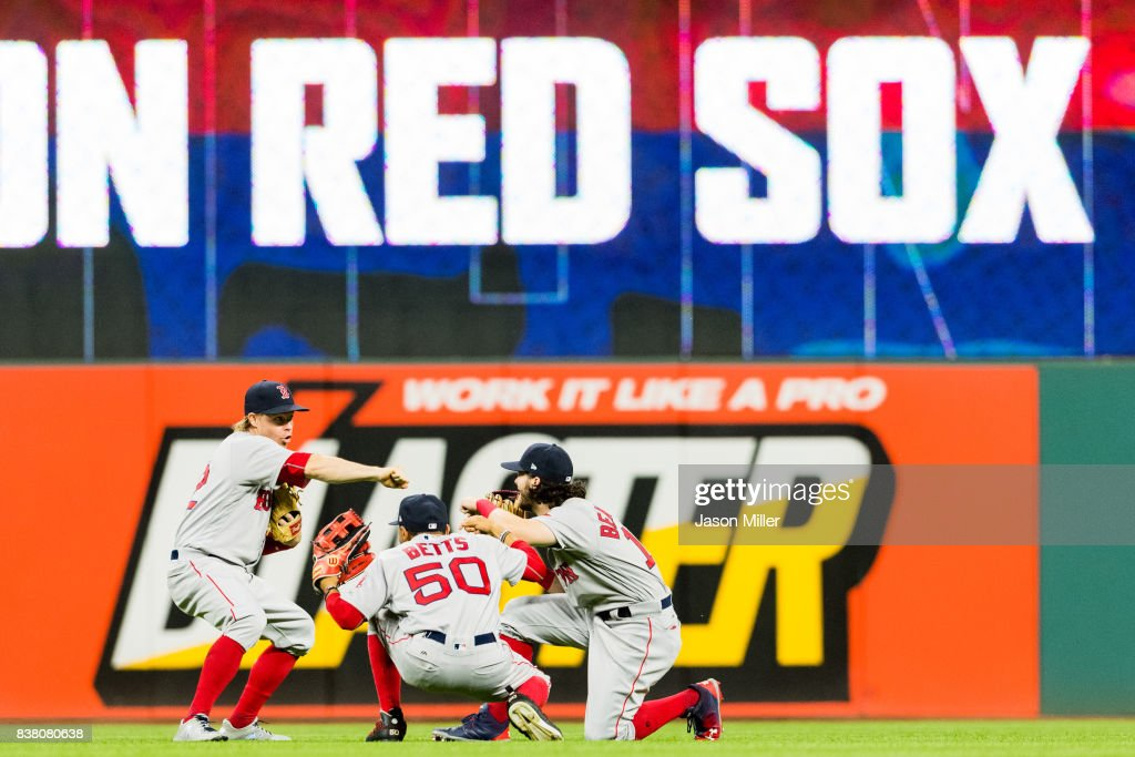 Outfielders Brock Holt #12 Mookie Betts #50 and Andrew Benintendi #16 of the Boston Red Sox celebrate after the Red Sox defeated the Cleveland Indians at Progressive Field on August 23, 2017 in Cleveland, Ohio. The Red Sox defeated the Indians 6-1.