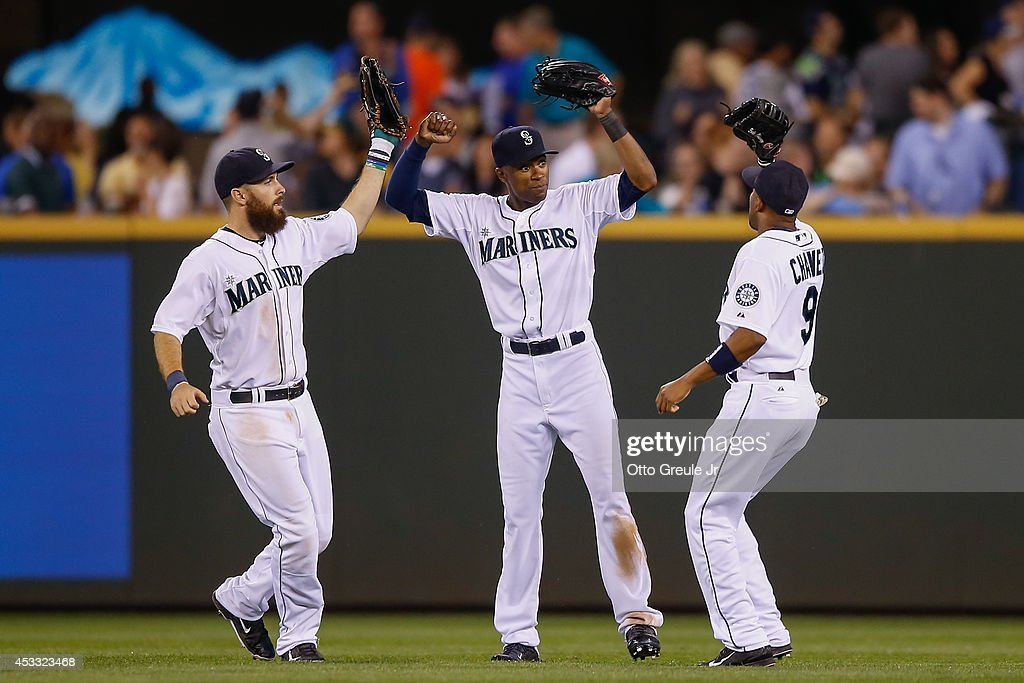 Outfielders Dustin Ackley #13 (L), Austin Jackson #16, and Endy Chavez #9 of the Seattle Mariners celebrate after defeating the Chicago White Sox 13-3 at Safeco Field on August 7, 2014 in Seattle, Washington.