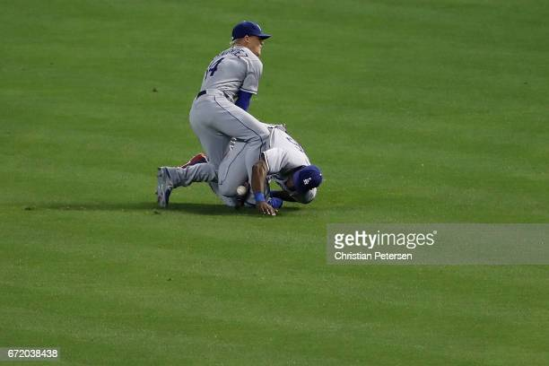Outfielders Enrique Hernandez and Yasiel Puig of the Los Angeles Dodgers collide as they attempt to catch a double hit by Jake Lamb of the Arizona...