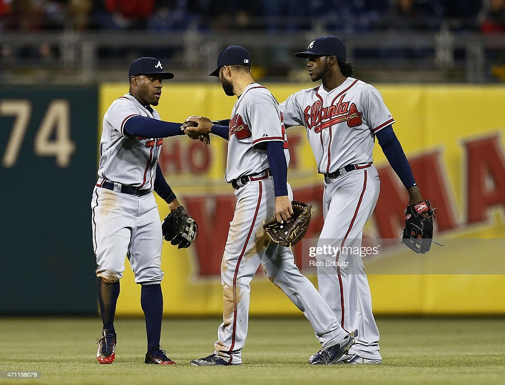 Outfielders Eric Young Jr. #4, Nick Markakis #22 and Cameron Maybin #25 of the Atlanta Braves congratulate each other after defeating the Philadelphia Phillies 5-3 at Citizens Bank Park on April 24, 2015 in Philadelphia, Pennsylvania.