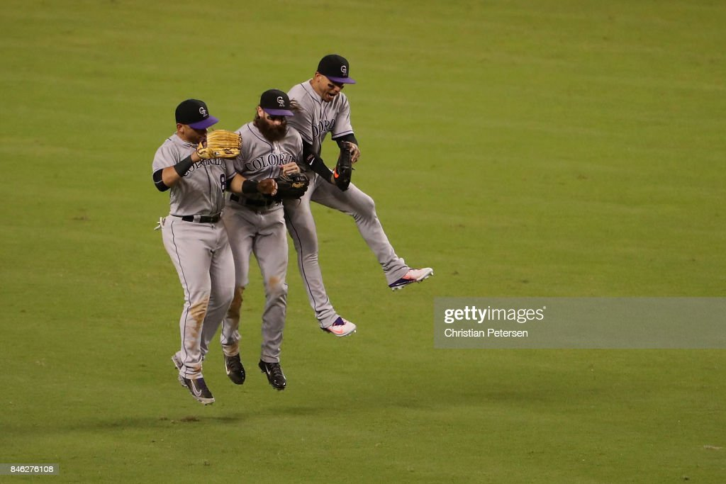 Outfielders Gerardo Parra #8, Charlie Blackmon #19 and Carlos Gonzalez #5 of the Colorado Rockies celebrate after defeating the Arizona Diamondbacks 4-2 in the MLB game at Chase Field on September 12, 2017 in Phoenix, Arizona.