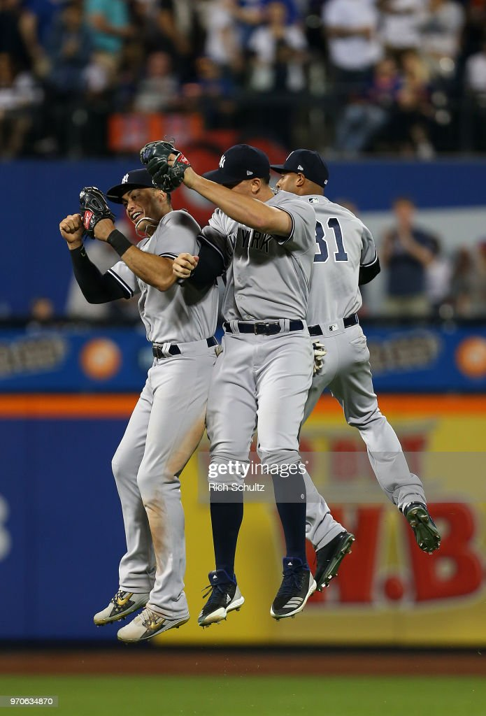 Outfielders Giancarlo Stanton #27, Aaron Judge #99 and Aaron Hicks #31 of the New York Yankees celebrate after defeating the New York Mets 4-3 in a game at Citi Field on June 9, 2018 in the Flushing neighborhood of the Queens borough of New York City.