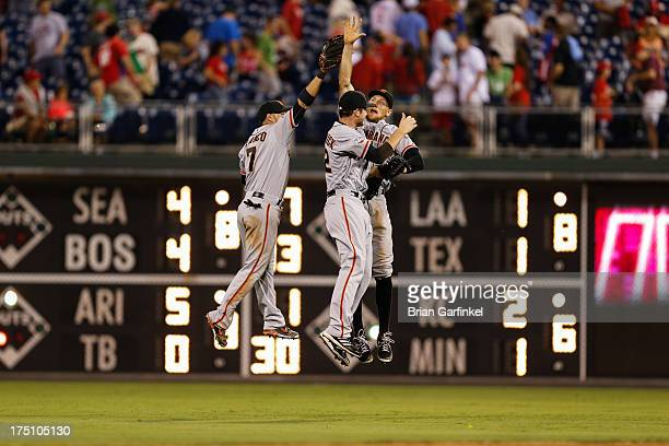 Outfielders Gregor Blanco Hunter Pence and Roger Kieschnick of the San Francisco Giants celebrate after the game against the Philadelphia Phillies at...