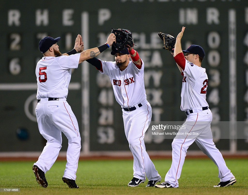 Outfielders Jonny Gomes #5, Shane Victorino #18 and Daniel Nava #29 of the Boston Red Sox celebrate a 6-2 win against the Tampa Bay Rays on July 23, 2013 at Fenway Park in Boston, Massachusetts.