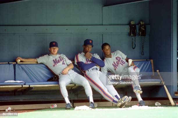 Outfielders Lenny Dykstra and Darryl Strawberry of the New York Mets flank pitcher Dwight Gooden as they look on from the dugout during a game...