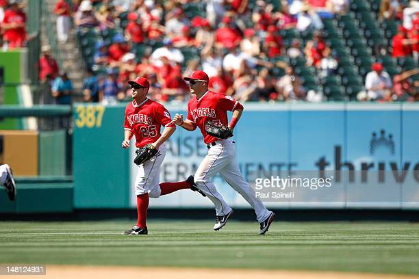 Outfielders Mike Trout of the Los Angeles Angels of Anaheim and Peter Bourjos of the Angels jog back to the dugout during the game against the Texas...