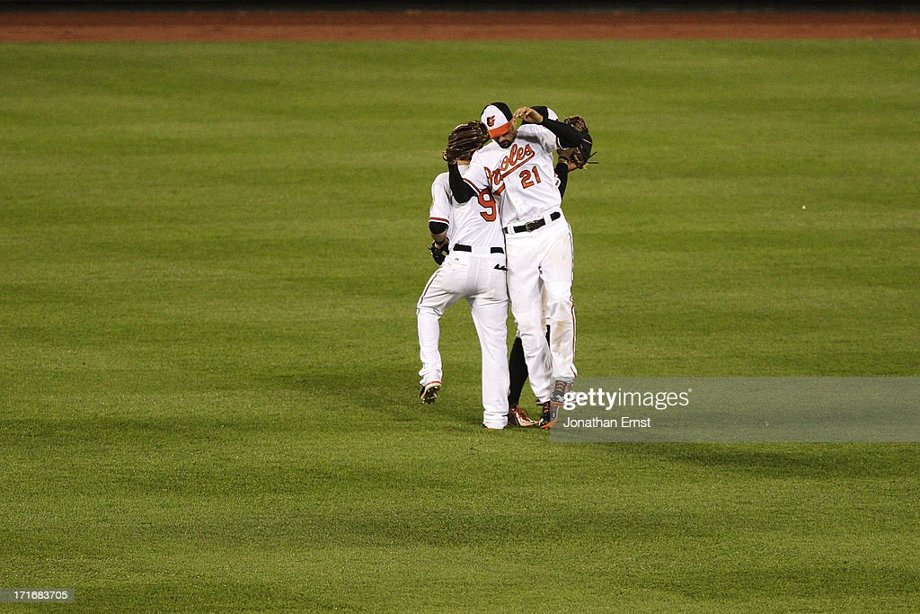 Outfielders Nate McLouth #9 (L), Nick Markakis #21 (R) and Adam Jones #10 (obscured) of the Baltimore Orioles celebrate at the end of their victory over the Cleveland Indians at Oriole Park at Camden Yards on June 27, 2013 in Baltimore, Maryland. The Baltimore Orioles won, 7-3.