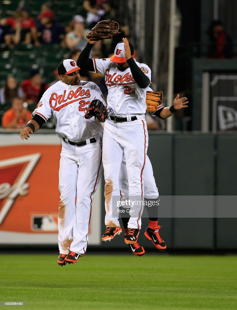 Outfielders Nelson Cruz #23, Nick Markakis #21 and David Lough #9 (R) of the Baltimore Orioles celebrate following the Orioles 4-0 win over the Boston Red Sox at Oriole Park at Camden Yards on June 9, 2014 in Baltimore, Maryland.