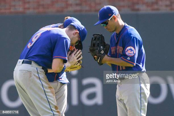 Outfielders Norichika Aoki right of the New York Mets Brandon Nimmoleft and Juan Lagares pay respects to each other after winning against the Atlanta...