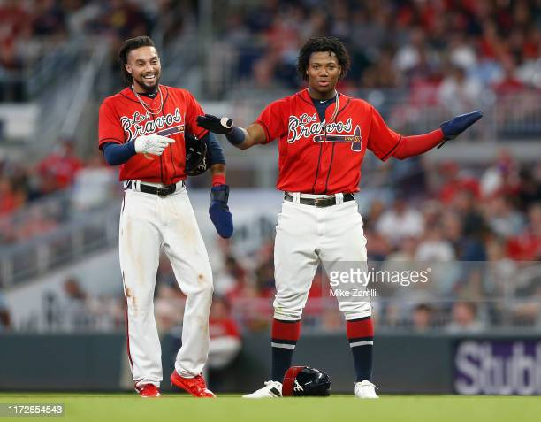 Outfielders Ronald Acuna Jr. #13 and Billy Hamilton of the Atlanta Braves unsuccessfully try to convince the replay crew to overturn an out call on a...