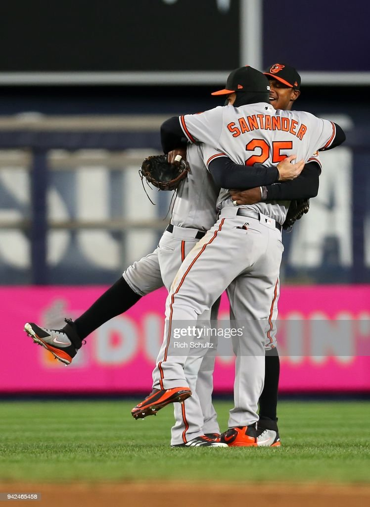 Outfielders Trey Mancini #16, Adam Jones #10 and Anthony Santander #25 of the Baltimore Orioles embrace after defeating the New York Yankees 5-2 in a game at Yankee Stadium on April 5, 2018 in the Bronx borough of New York City.