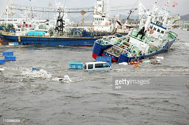 OUTFishing boats and vehicles are carried by a tsunami wave at Onahama port in Iwaki city in Fukushima prefecture northern Japan on March 11 2011 A...