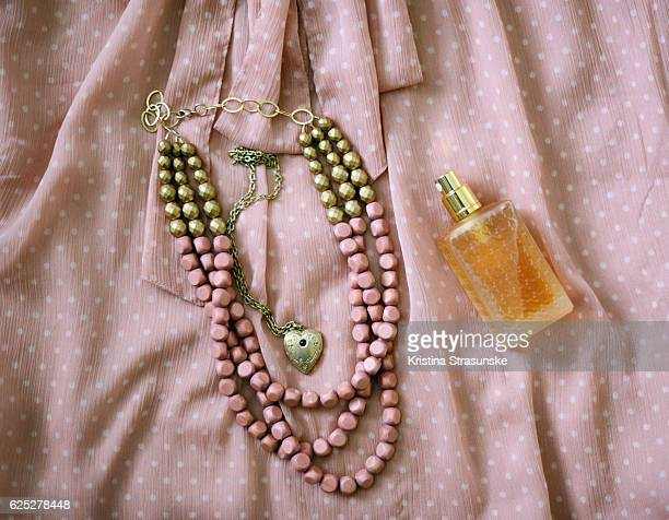 outfit of the day, blouse, two necklaces and a perfume bottle