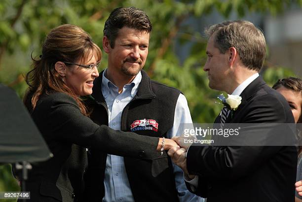 Outgoing Alaska Governor Sarah Palin and her husband Todd congratulate incoming Governor Sean Parnell during the annual Governor's Picnic July 26...