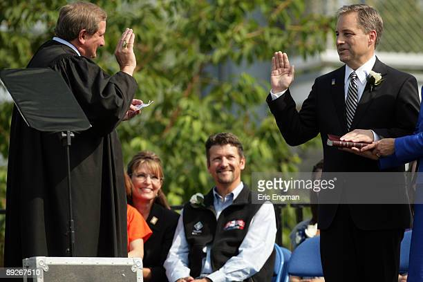 Outgoing Alaska Governor Sarah Palin her husband Todd look on as incoming Governor Sean Parnell is sworn in by Supreme Court Justice Daniel Winfree...