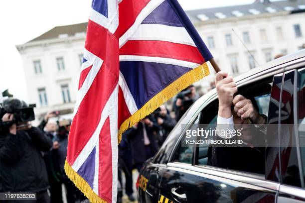 Outgoing British MEP Jonathan Bullock sitting in a taxi holds the Union Jack flag as he and other British pro-Brexit MEPS leave Brussels on January...