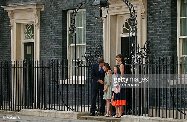 Outgoing British prime minister David Cameron hugs his daughter Nancy Gwen as he stands with his family outside 10 Downing Street in central London...