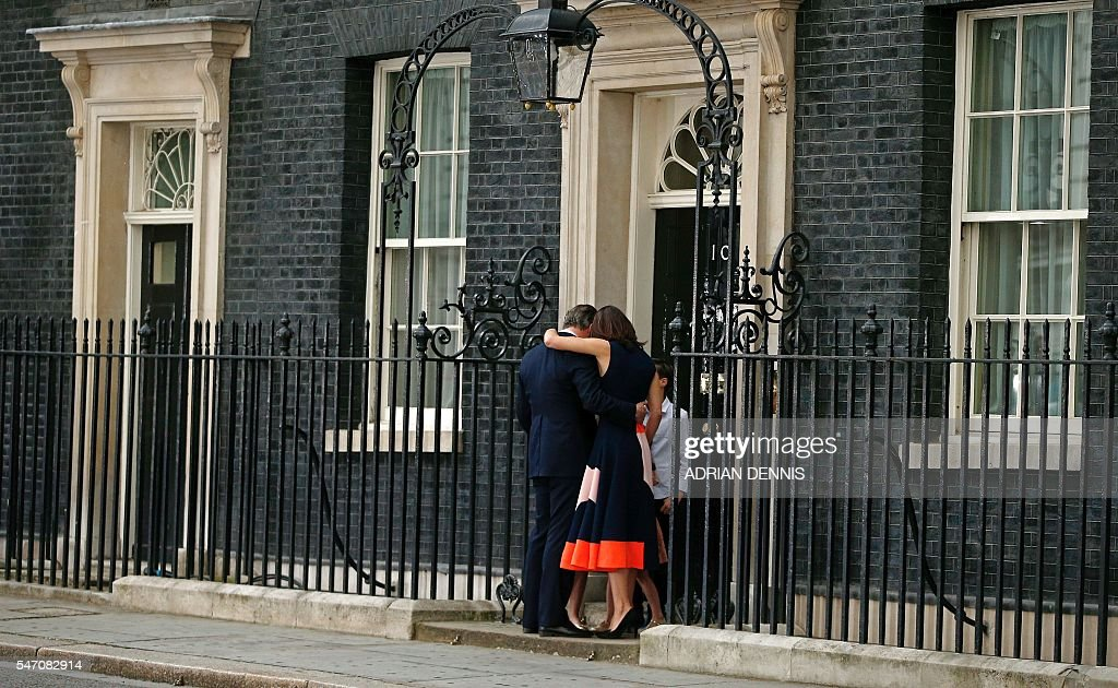 TOPSHOT - Outgoing British prime minister David Cameron is hugged by his wife Samantha outside 10 Downing Street with his family behind, in central London on July 13, 2016 before going to Buckingham Palace to tender his resignation to Queen Elizabeth II. Outgoing British prime minister David Cameron urged his successor Theresa May on Wednesday to maintain close ties with the EU even while negotiating to leave it, as he paid a fond farewell to MPs hours before leaving office. Cameron will tender his resignation on July 13 to Queen Elizabeth II at Buckingham Palace, after which the monarch will task the new leader of the Conservative Party Theresa May with forming a government. DENNIS