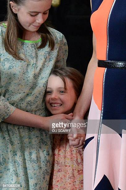 Outgoing British prime minister David Cameron speaks as his daughter Florence Rose Endellion is hugged by his other daughter Nancy Gwen outside 10...