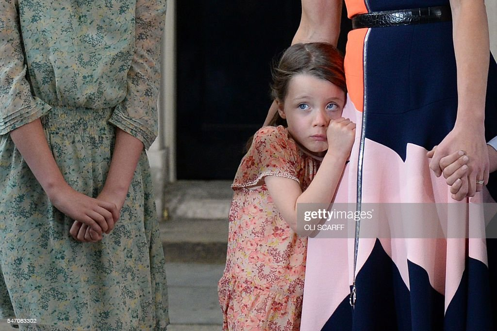 TOPSHOT - Outgoing British prime minister David Cameron (not pictured) speaks as his daughter Florence Rose Endellion hangs onto her mother, Samantha Cameron outside 10 Downing Street in central London on July 13, 2016 before going to Buckingham Palace to tender his resignation to Queen Elizabeth II. Outgoing British prime minister David Cameron urged his successor Theresa May on Wednesday to maintain close ties with the EU even while negotiating to leave it, as he paid a fond farewell to MPs hours before leaving office. Cameron will tender his resignation on July 13 to Queen Elizabeth II at Buckingham Palace, after which the monarch will task the new leader of the Conservative Party Theresa May with forming a government. SCARFF